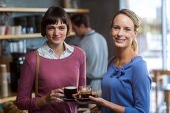 Amis féminins agissant l'un sur l'autre tout en ayant une tasse de café dans le café Images stock