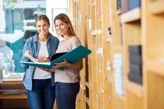 Amis féminins analysant le grand livre dans le magasin Photos libres de droits