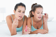 Amis féminins appliquant le maquillage dans le lit Photographie stock
