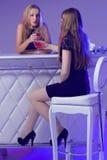 Amis féminins appréciant des cocktails dans une boîte de nuit Photographie stock
