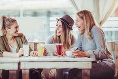 Amis féminins appréciant en conversation et café potable en café Photographie stock