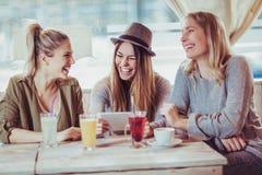 Amis féminins appréciant en conversation et café potable en café Photo stock