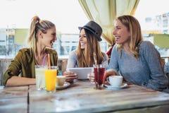 Amis féminins appréciant en conversation et café potable en café Images stock