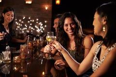 Amis féminins appréciant la nuit à la barre de cocktail Photographie stock