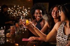 Amis féminins appréciant la nuit à la barre de cocktail Photographie stock libre de droits