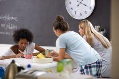 Amis féminins appréciant le petit déjeuner tout en vérifiant des téléphones portables Image libre de droits
