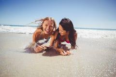 Amis féminins appréciant sur la plage Image stock