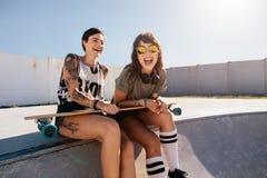 Amis féminins appréciant un jour au parc de patin Image libre de droits