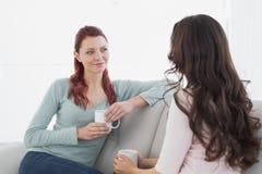 Amis féminins appréciant une causerie au-dessus de café à la maison Image stock