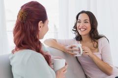 Amis féminins appréciant une causerie avec des tasses de café à la maison Images stock