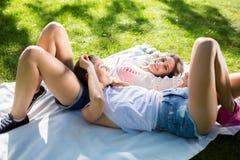 Amis féminins assez heureux se trouvant sur la couverture en parc Images stock