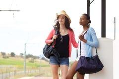Amis féminins attendant le train à la gare Image libre de droits