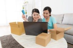 Amis féminins attirants heureux employant la carte de crédit Photographie stock libre de droits