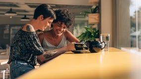 Amis féminins au café utilisant le téléphone portable Photo libre de droits