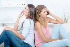 Amis féminins au téléphone les uns contre les autres Photos libres de droits