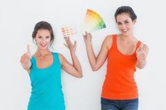 Amis féminins avec des échantillons de couleur faisant des gestes des pouces  Photographie stock libre de droits