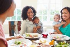 Amis féminins avec des bébés appréciant le repas à la maison ensemble Photo stock