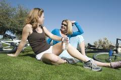 Amis féminins avec des bicyclettes détendant en parc Photo stock