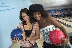 Amis féminins avec des boules dans le bowling Photos stock
