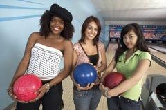Amis féminins avec des boules dans le bowling Photos libres de droits
