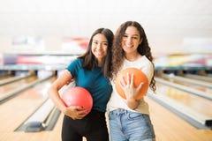 Amis féminins avec des boules de bowling traînant dans l'allée Photos libres de droits