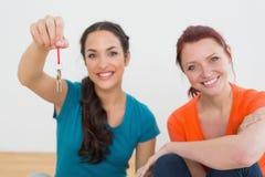 Amis féminins avec des clés dans la nouvelle maison Images stock