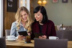 Amis féminins avec des comprimés de Digital chez Coffeeshop Images libres de droits