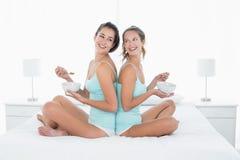 Amis féminins avec des cuvettes se reposant de nouveau au dos sur le lit Photo libre de droits