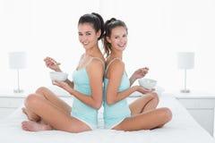 Amis féminins avec des cuvettes se reposant de nouveau au dos sur le lit Image stock