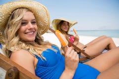 Amis féminins avec des glaces à l'eau semblant parties tout en se reposant sur la chaise de plate-forme Photographie stock libre de droits