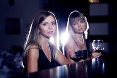 Amis féminins avec des glaces de vin Image stock