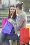 Amis féminins avec des paniers communiquant tout en se reposant sur le banc Images stock