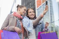 Amis féminins avec des paniers prenant l'autoportrait par le téléphone portable Photo libre de droits