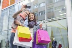 Amis féminins avec des paniers prenant l'autoportrait par le téléphone portable contre le magasin Photos libres de droits