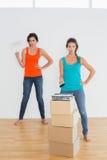 Amis féminins avec des pinceaux dans une nouvelle maison Photos libres de droits