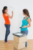 Amis féminins avec des pinceaux dans une nouvelle maison Photo stock