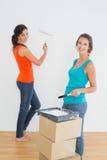 Amis féminins avec des pinceaux dans une nouvelle maison Photos stock