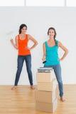 Amis féminins avec des pinceaux dans une nouvelle maison Images stock