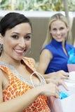 Amis féminins avec des sacs à provisions au restaurant Image stock