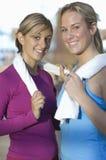 Amis féminins avec des serviettes au gymnase Photos stock