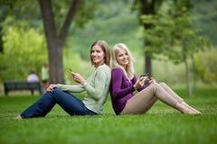 Amis féminins avec des téléphones portables en parc Photo stock