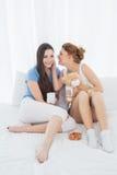 Amis féminins avec des tasses de café bavardant dans le lit Photographie stock libre de droits