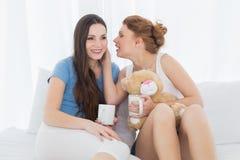 Amis féminins avec des tasses de café bavardant dans le lit Image stock