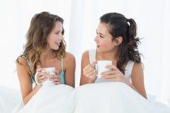 Amis féminins avec des tasses de café causant dans le lit Images stock