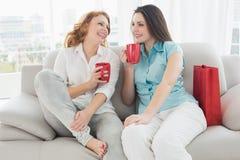 Amis féminins avec des tasses de café conversant à la maison Photos stock