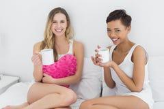 Amis féminins avec des tasses de café dans le lit Photographie stock libre de droits