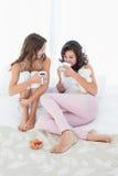 Amis féminins avec des tasses de café dans le lit Photos libres de droits