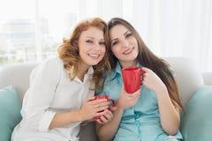 Amis féminins avec des tasses de café dans le salon Photos stock