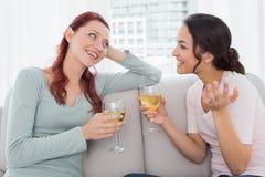 Amis féminins avec des verres de vin causant à la maison Images stock