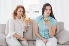 Amis féminins avec des verres de vin se reposant sur le sofa Photographie stock libre de droits
